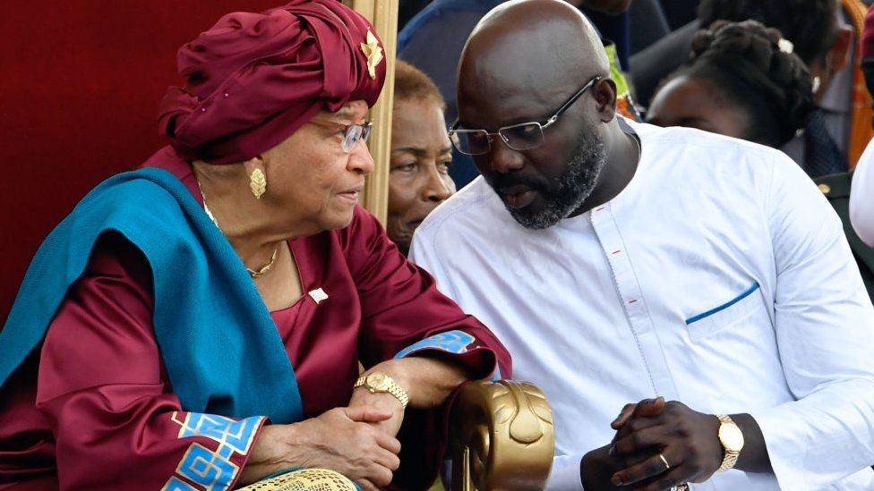 Liberia's outgoing president Ellen Johnson Sirleaf (L) listens to Liberia's President-elect George Weah, during Weah's swearing-in ceremony on January 22, 2018