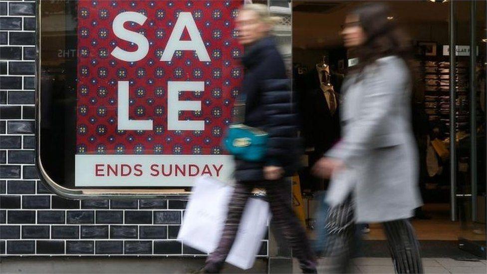 Women walking past a sale sign