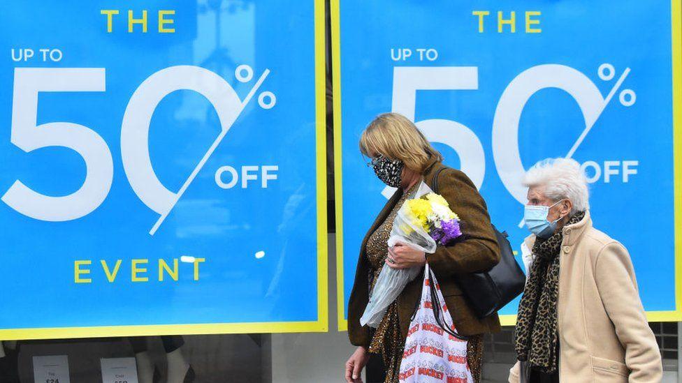 Shoppers walking past window