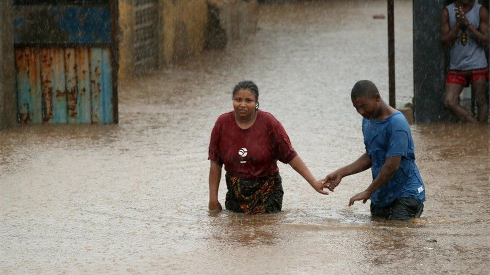 Two people wade through rising floodwaters in Pemba, Mozambique after Cyclone Kenneth struck the African nation