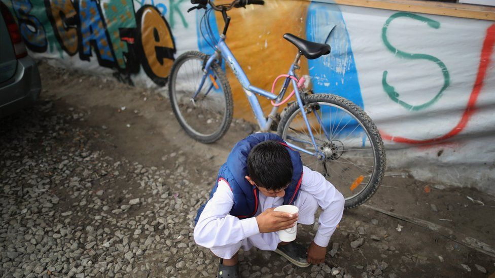 Boy drinks tea outside a cafe in the 'Jungle' migrant camp