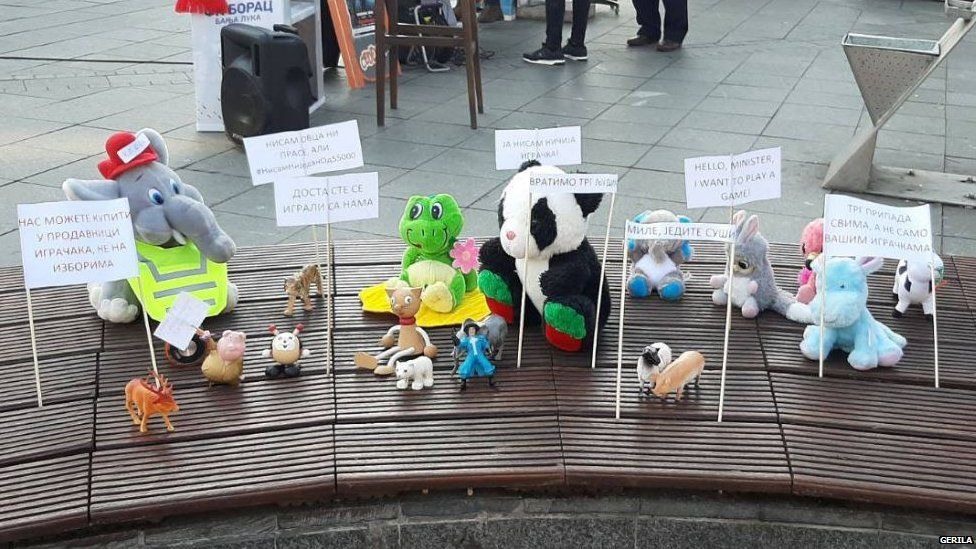 Soft toys arranged on a bench with protest slogans in Banja Luka