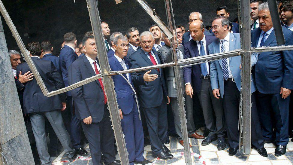 Turkey's Prime Minister Binali Yildirim (C) visits damaged parts of the Turkish parliament in Ankara, Turkey on Tuesday