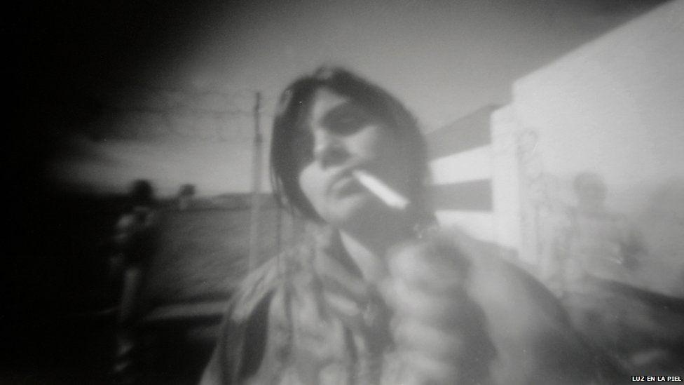 A pinhole photograph of a woman smoking
