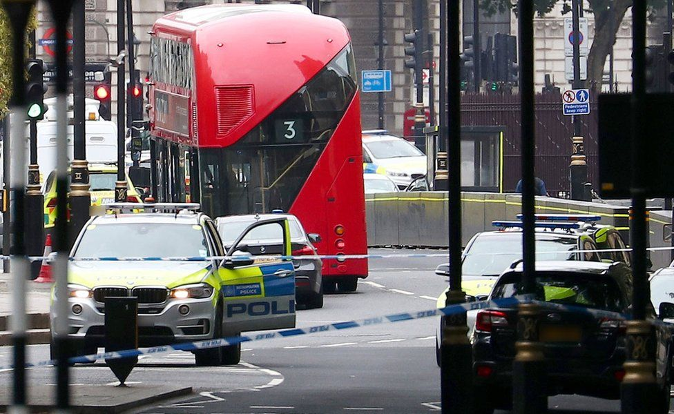A car that crashed outside the Houses of Parliament surrounded by members of the emergency services in Westminster