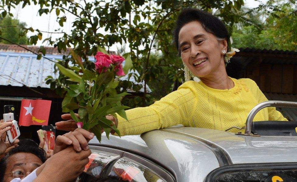 Myanmar opposition leader Aung San Suu Kyi receives roses from a supporter during a campaign rally for the National League for Democracy (NLD) in Kawhmu on the outskirts of Yangon on 24 October 2015.
