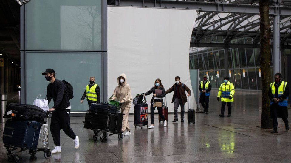 Travellers are escorted to a hotel to quarantine