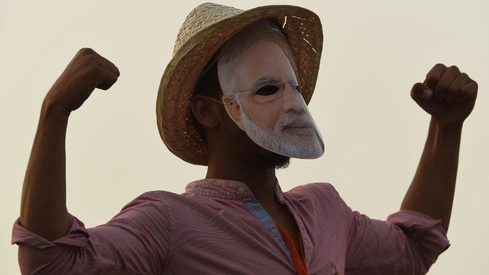 Bharatiya Janata Party (BJP) supporter gestures as Indian Prime Minister Narendra Modi (not pictured) delivers a speech during a rally ahead of Phase VI of India's general election in New Delhi on May 8, 2019.