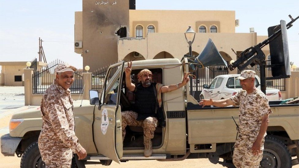 Libyan pro-government forces celebrate on tank after taking back the city of Misrata from IS
