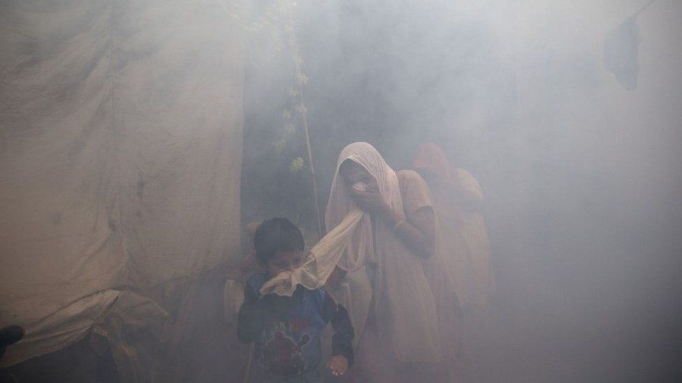 Residents cover their face and run in smoke as a municipal worker fumigates a residential area to prevent mosquitoes from breeding in New Delhi, India, Monday, Sept. 7, 2015