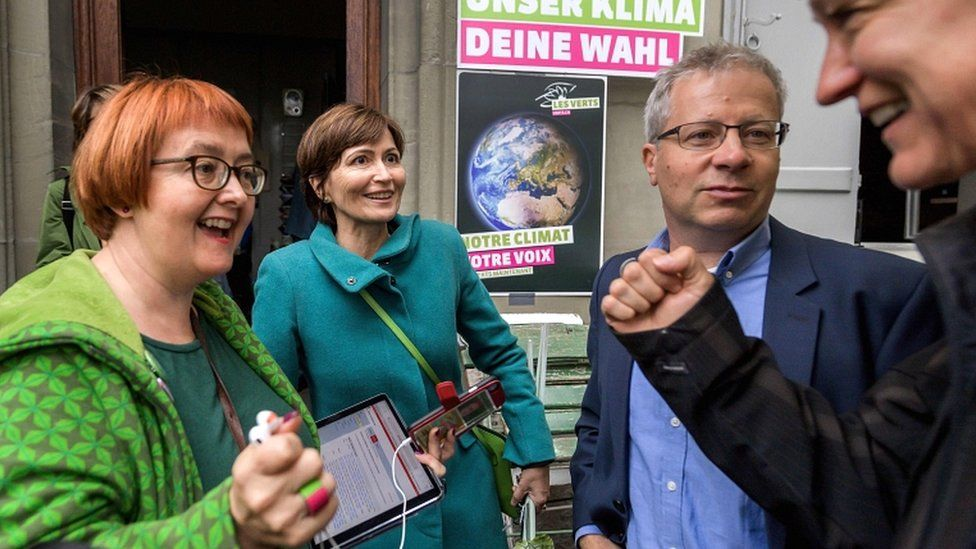 Swiss Green Party president MP Regula Rytz (2nd L) reacts with party members at their meeting place waiting for the first results during the general election in the Swiss capital, Bern.