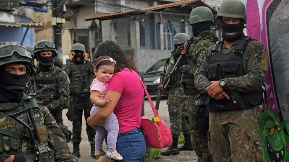 A woman carries her child as she walks past military police on patrol near the Vila Kennedy favela in Rio de Janeiro on February 23, 2018.
