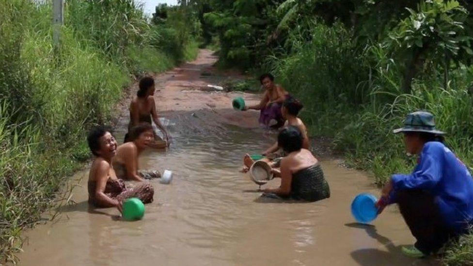 Grannies take bath in potholes