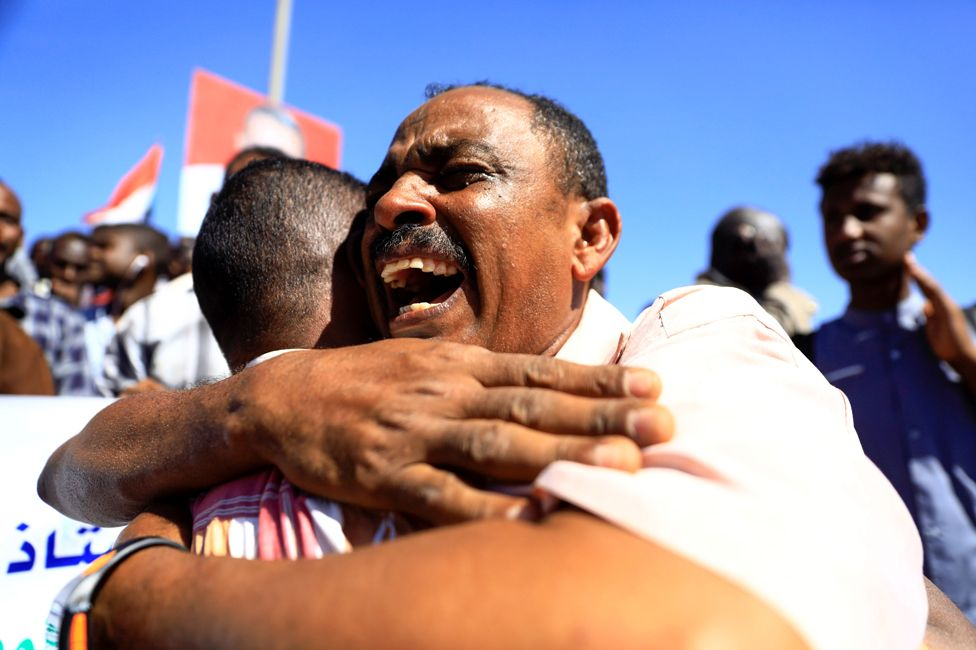 Sudanese civilians hug each other after the sentencing of 27 members of the national intelligence service to death by hanging over the killing of a teacher in detention in February during protests that led to the overthrow of former president Omar al-Bashir