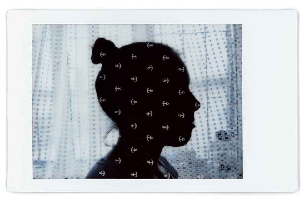 A composite image showing the profile of Liudmila with a patterned baby blanket over the top
