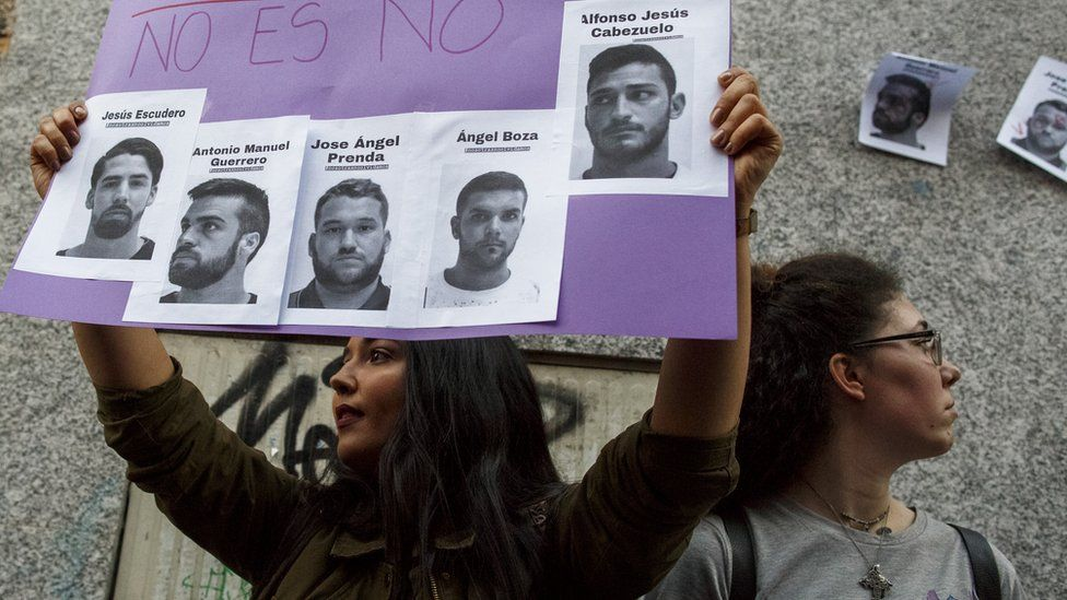 """A woman holds aloft a poster during a demonstration - on it are the photographs of the """"wolf pack"""" with the Spanish words for """"no is no"""""""