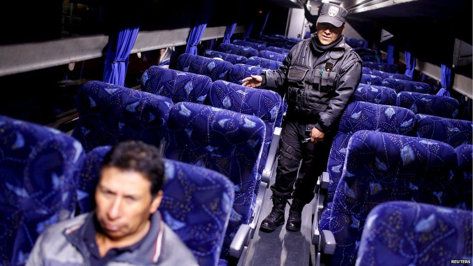 """A policeman inspects a passenger bus at a checkpoint outside the Altiplano Federal Penitentiary, after drug lord Joaquin """"El Chapo"""" Guzman escaped"""