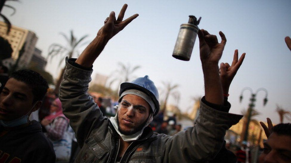 An Egyptian protester holds a tear gas cannister