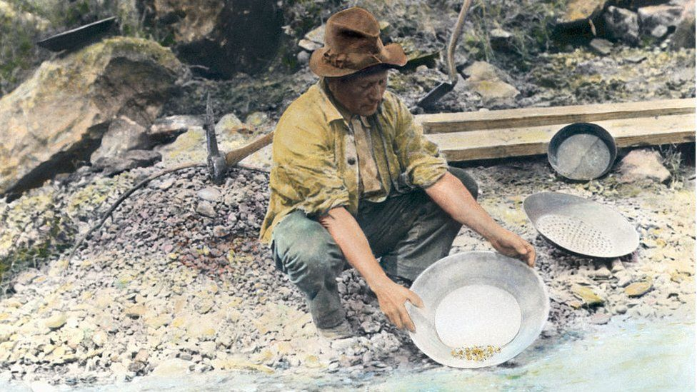 A prospector pans for gold in northern California. Hand tinted photograph, circa 1890.
