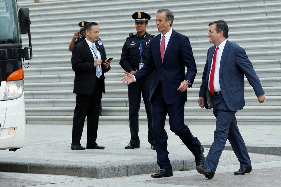 US Senators John Thune (R-SD) and Ted Cruz (R-TX), (R), walk to a Senate caravan bus from Capitol Hill to attend a North Korea briefing at the White House, in Washington, 26 April