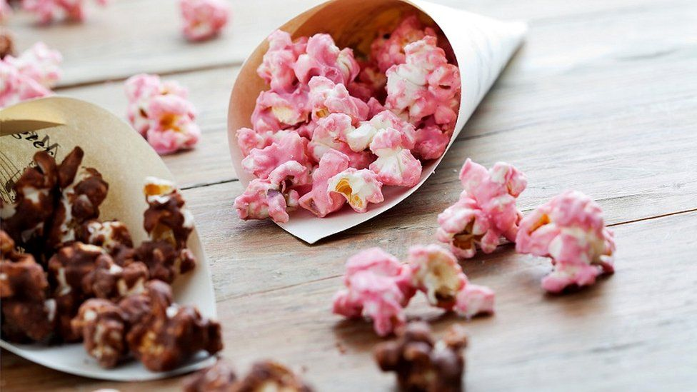 Strawberry & chocolate popcorn spilling onto wooden surface