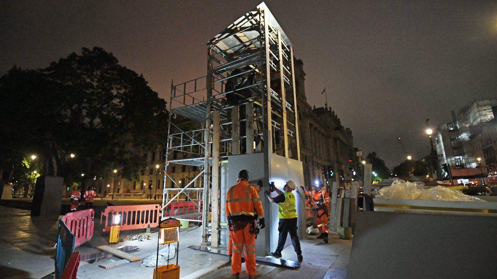 Scaffolders erect boarding around the statue of Sir Winston Churchill in Parliament Square, London