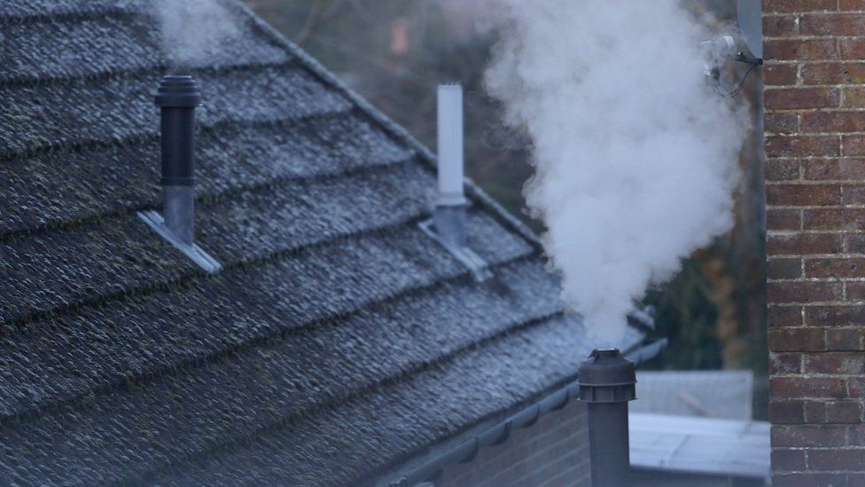 Smoke rising from chimney's on a cold day