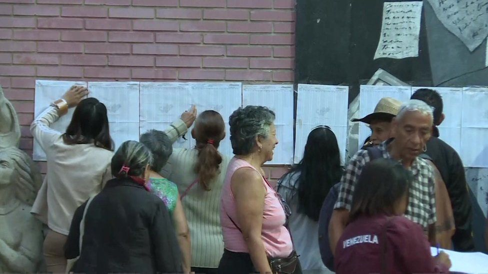 Voters look at lists outside a polling station