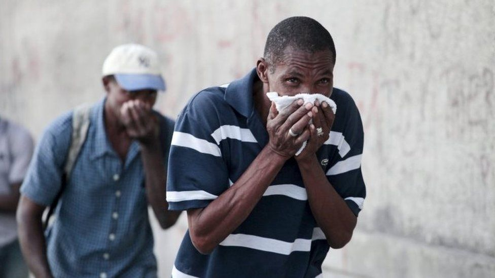 A man covers his face to protect himself from tear gas after clashes between residents and protesters in a demonstration against the results of the presidential elections in Port-au-Prince on 24 November, 2015