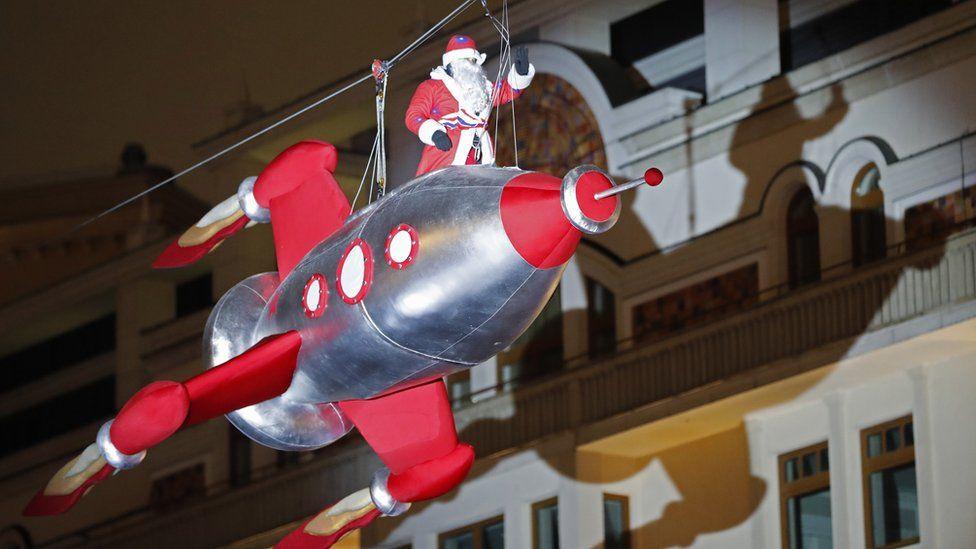 Человек в костюме Деда Мороза на ракете