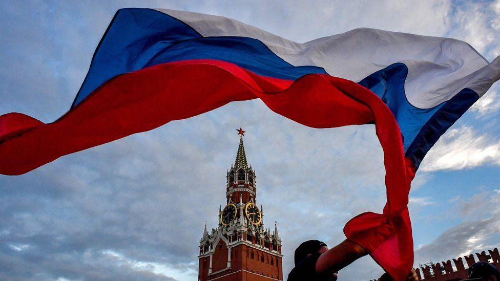 A Russia fan waves the Russian national flag as fans celebrate at the Red Square in Moscow