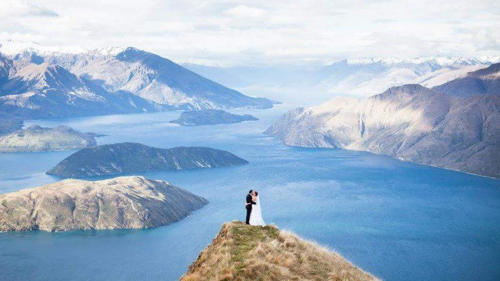 Aerial photograph of Kristy and Corey Rousseau in their wedding outfits on top of Roy's Peak in New Zealand