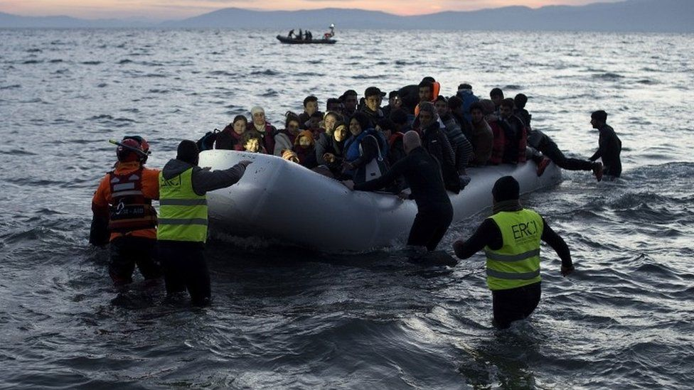 Volunteers and lifeguards help an inflatable boat with migrants after crossing the sea from Turkey to Lesbos, 12 March