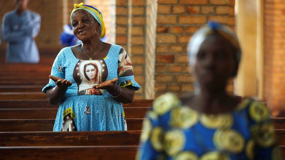 A woman prays during a mass for a peaceful elections at the Notre Dame de Kinshasa cathedra