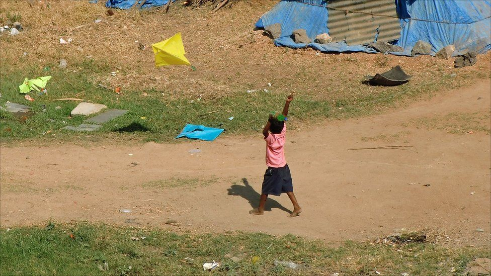 A young boy flying a kite in India