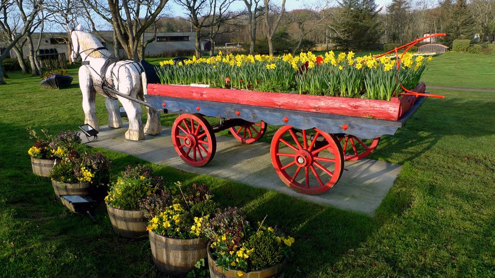 Horse statue and a cart of daffodils