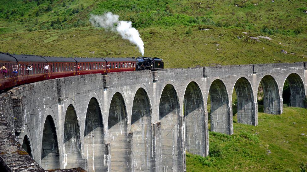 Steam train crossing Glenfinnan Viaduct