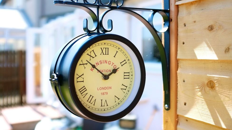 Clock hanging from a garden shed