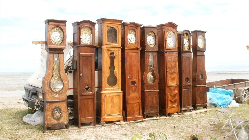 A row of grandfather clocks for sale at an outdoor market in France.