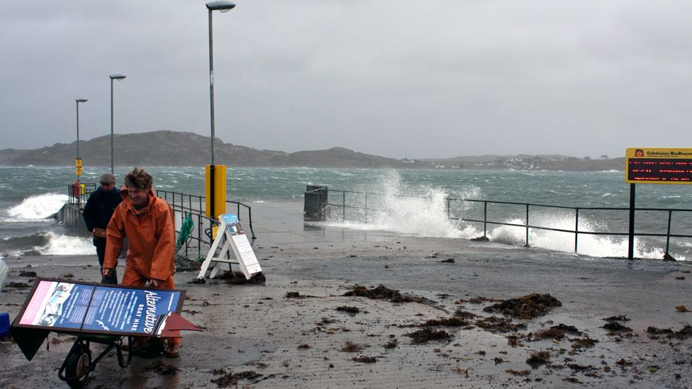 Men taking a sign down as waves break on the jetty
