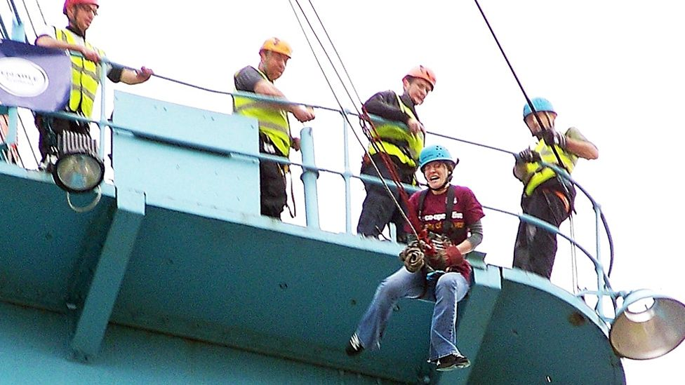 Woman about to swing off a crane