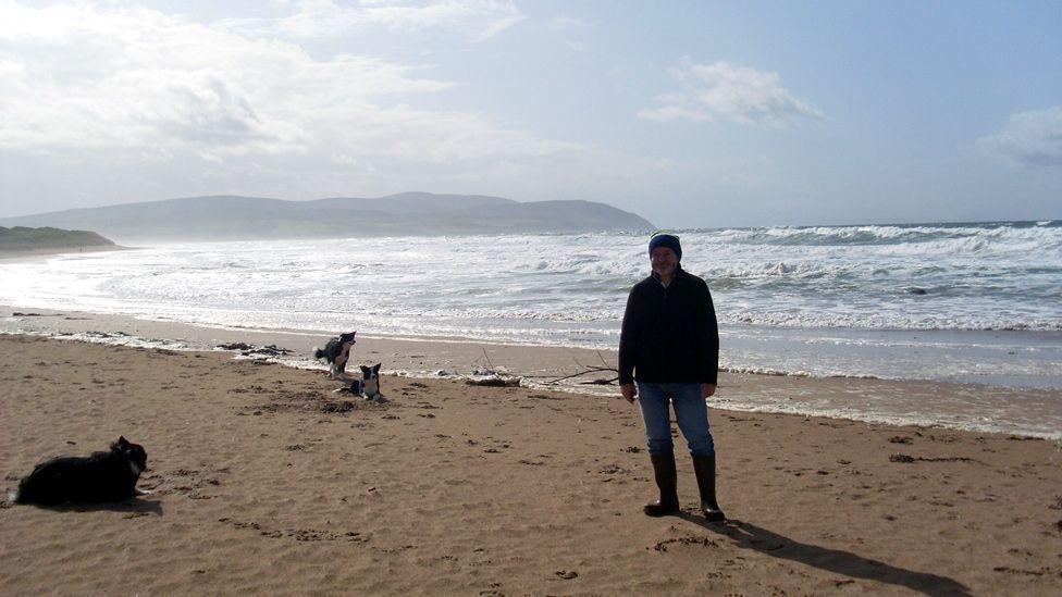 Martin and three Border collies on the beach