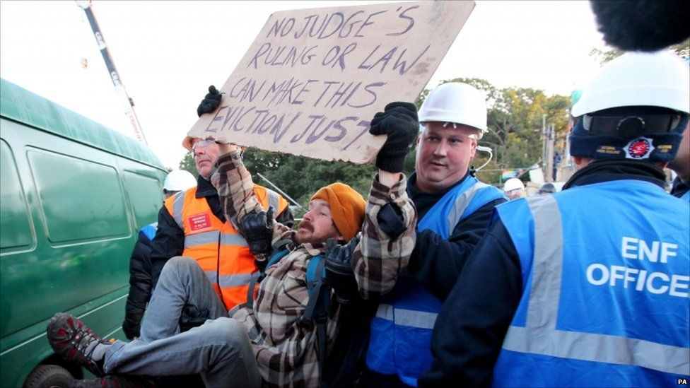 """An Enforcement Officer and a Security Officer remove a protester at Dale Farm in Essex where supporters have clashed with riot police at the UK""""s largest illegal travellers"""" site as the planned eviction got under way on 19 October"""