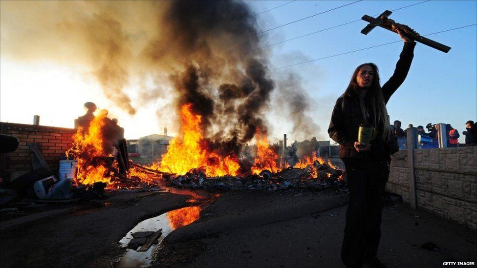 A traveller holds aloft a crucifix as a caravan burns on Dale Farm, near Basildon, east of London, on October 19, 2011