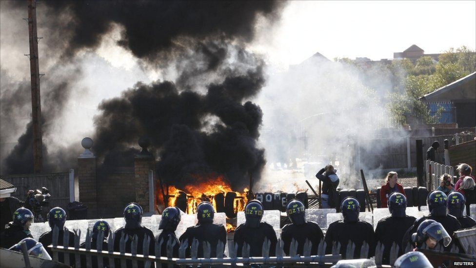 A barricade burns in front of a line of riot police at the Dale Farm Traveller site near Billericay, southern England 19 October 2011