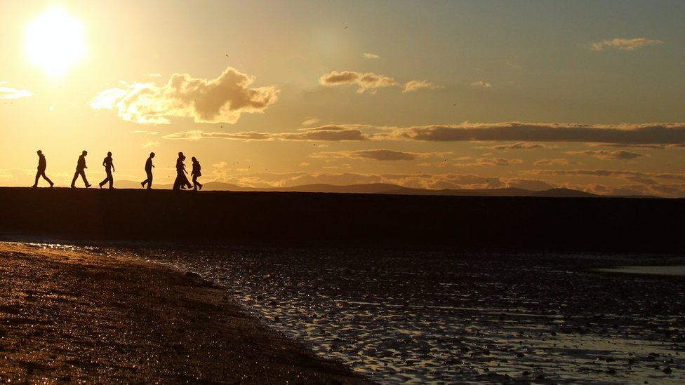People walking on Cramond beach in Edinburgh as the sun sets