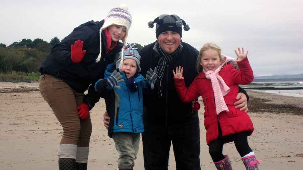Family on the beach waving at the camera