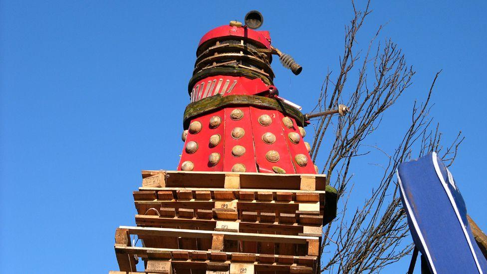 Dalek on top of wooden pallets