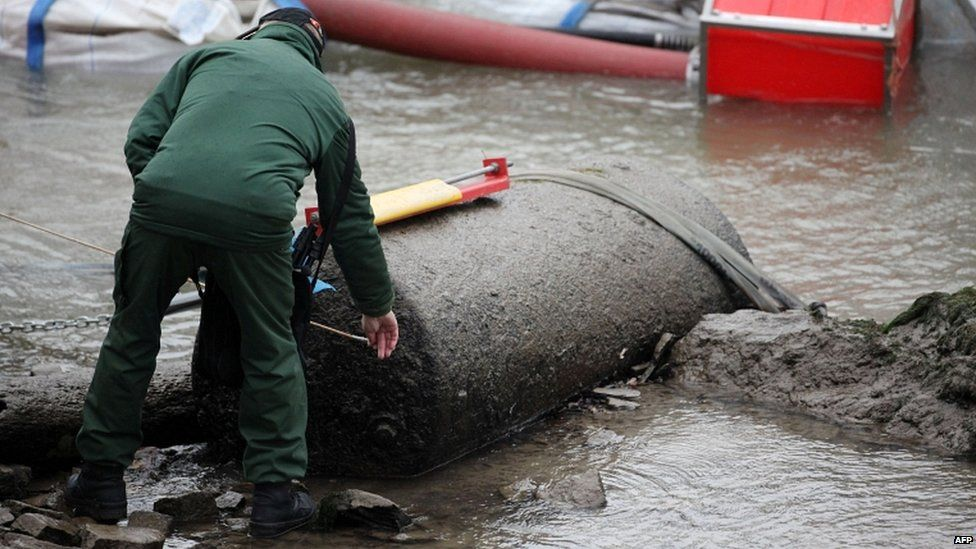 A member of the Rhineland-Palatinate bomb disposal team inspect a bomb in the Rhine in Koblenz, Germany, on 4 December 2011