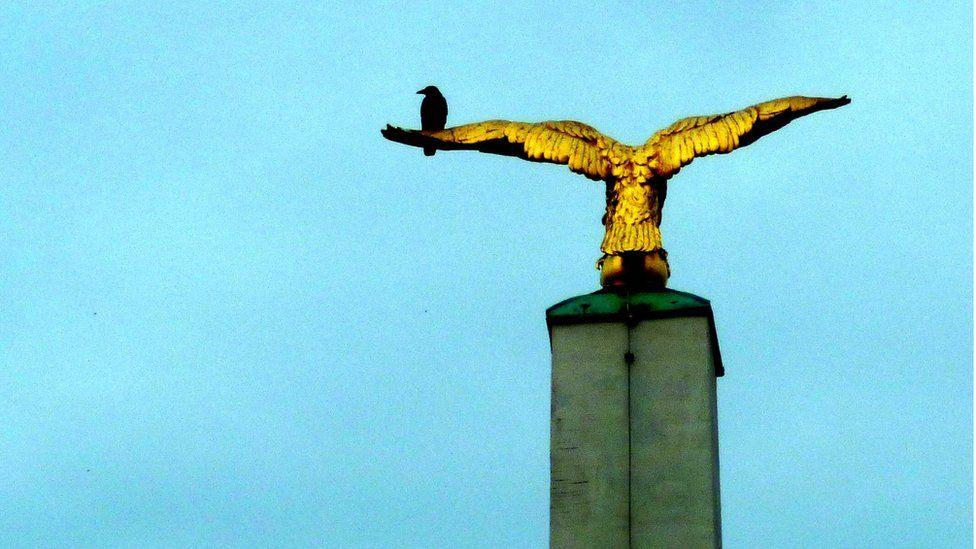 A crow on a statue of an eagle